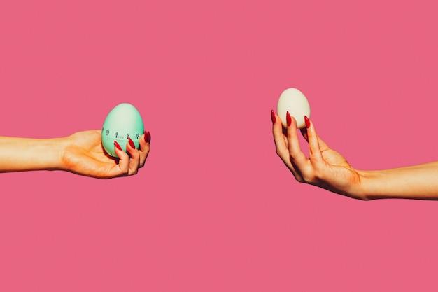 Jajka. kolaż sztuki współczesnej w stylu pop-art. ręce na białym tle na modnym kolorowym tle z copyspace, kontrast. nowoczesny design z copyspace na reklamę. modne kolory.