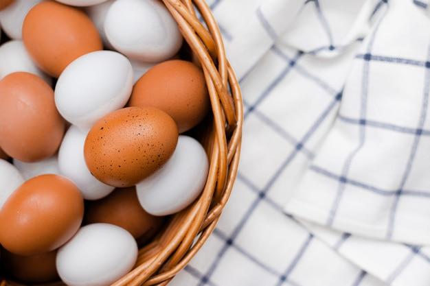 Jajka kurze na sprawdzonym ręczniku kuchennym na lekkim stole. koncepcja produktów rolnych i naturalnej żywności. produkty domowe. świeże jaja kurze.