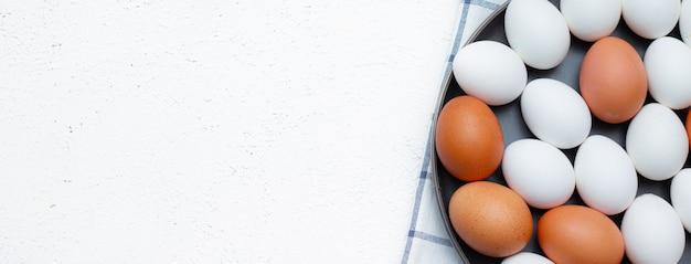 Jajka kurze na sprawdzonym ręczniku kuchennym na lekkim stole. koncepcja produktów rolnych i naturalnej żywności.