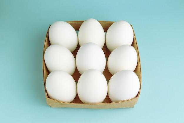 Jajka kurze w drewnianym opakowaniu. dziewięć białych jaj w kwadratowym pudełku