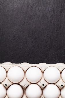 Jajka kurze w paczce na czarnym stole