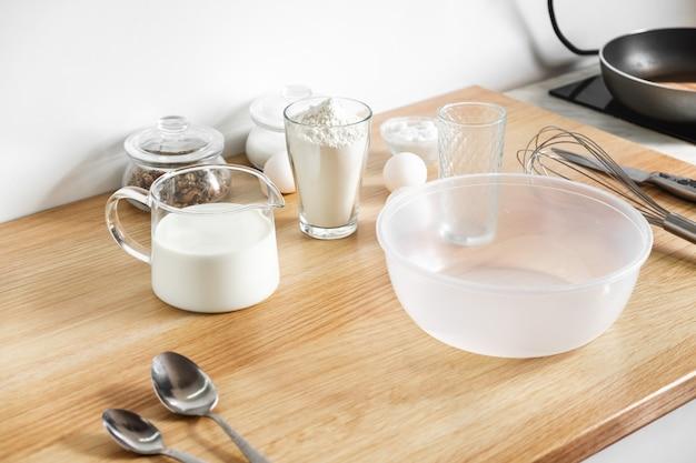 Jajka, mąka karafka z mlekiem na stole i trzepaczka