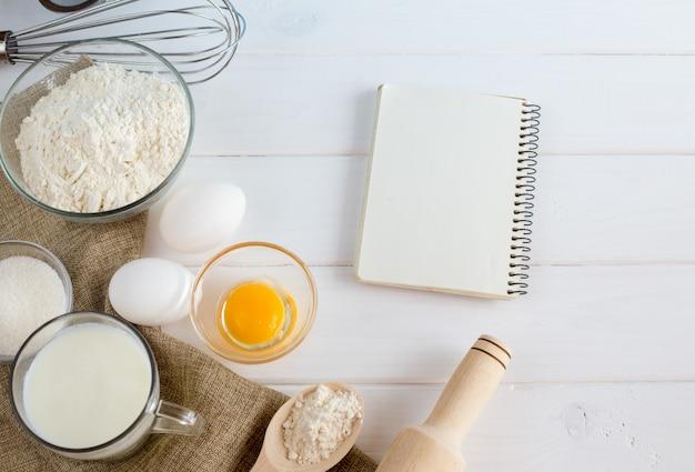 Jajka, mąka, mleko, z trzepaczką na białym drewnianym stole z góry.