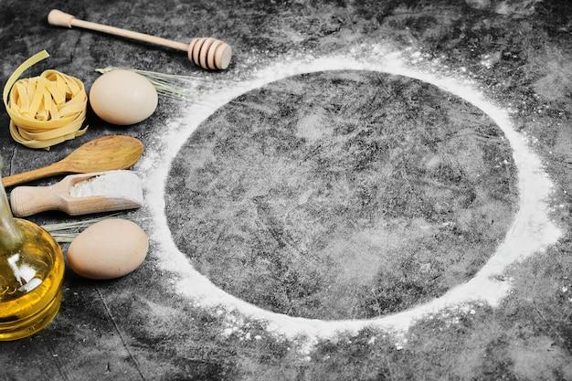 Jajka, mąka, olej, surowy makaron, drewniane łyżki na marmurze.