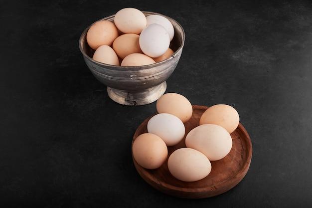 Jajka na drewnianym talerzu i metalowej filiżance.
