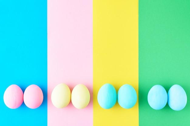 Jajka na kolorowym pasiastym tle, odgórny widok, minimalizmu pojęcie