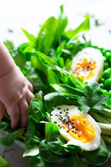 Jajka na miękko z sałatą, dzikim czosnkiem, zielonym groszkiem i natką pietruszki. koncepcja zdrowego odżywiania. wegańskie. ręka dziecka wprowadzona do miski z sałatką. bądź zdrowy od dzieciństwa