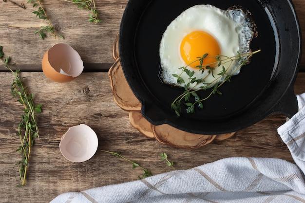 Jajka na patelni na drewnianym stole