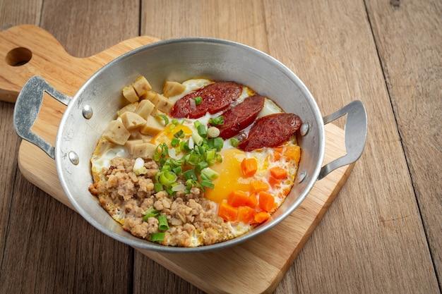 Jajka na patelni posypane chińską kiełbasą, pokrojony w kostkę boczek, śniadanie.