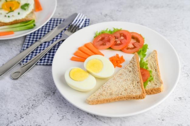 Jajka na twardo, chleb, marchewki i pomidory na białym talerzu z nożem i widelcem.