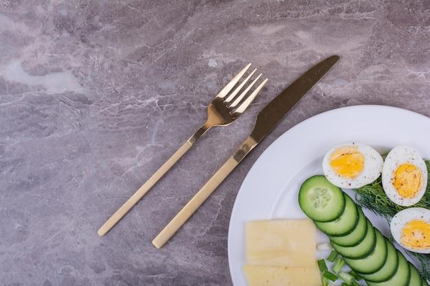 Jajka na twardo z mielonymi ziołami i ogórkami na białym talerzu