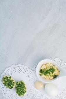 Jajka na twardo z zielenią na białym tle.