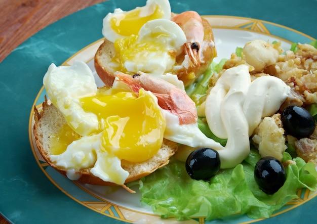 Jajka neptuna. warstwowe danie śniadaniowe składające się z angielskiej muffinki, jajek w koszulce i sosu holenderskiego