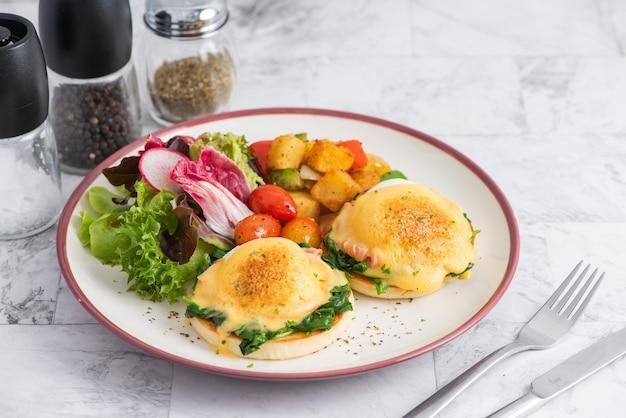 Jajka po benedyktyńsku na angielskiej muffinie z wędzonym łososiem, mixem sałat i sosem holenderskim na białej desce