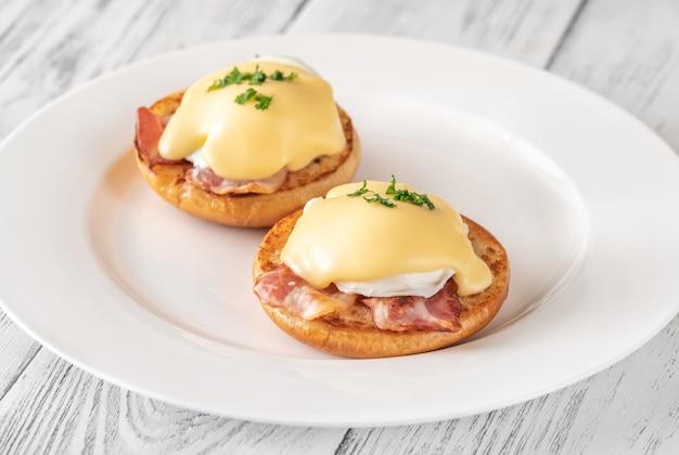 Jajka po benedyktyńsku z boczkiem na białym talerzu