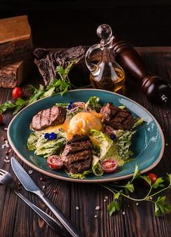 Jajka po benedyktyńsku z mięsem wołowym na dużym białym talerzu