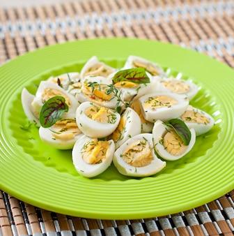 Jajka przepiórcze gotowane połówki na zielonym talerzu