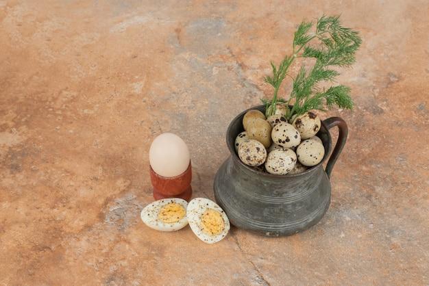 Jajka przepiórcze na filiżance w marmurowym stole.