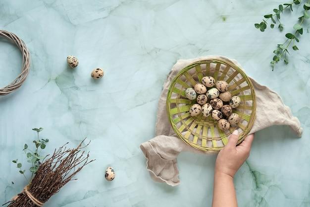 Jajka przepiórcze, naturalne wiosenne dekoracje i gałązki eukaliptusa. mieszkanie leżało na stole z marmuru w kolorze miętowej zieleni.