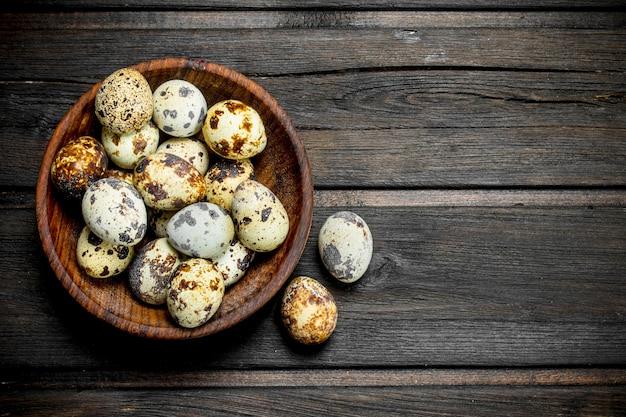 Jajka przepiórcze w misce. na drewnianej powierzchni.