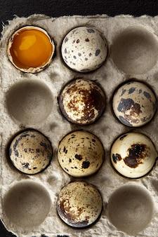 Jajka przepiórcze w tekturowym opakowaniu na szarym porysowanym stole.