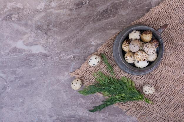 Jajka przepiórcze z ziołami w metalowej filiżance.