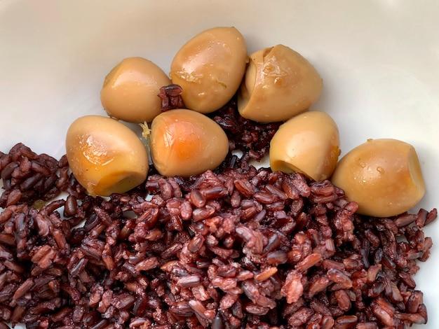 Jajka przepiórcze zbliżenie słodki duszony (kai palo) z ryżem riceberry w misce whote, domowe gotowanie, tajskie jedzenie