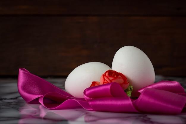 Jajka, różowa taśma, kwiaty na powierzchni drewnianej. wielkanocna koncepcja
