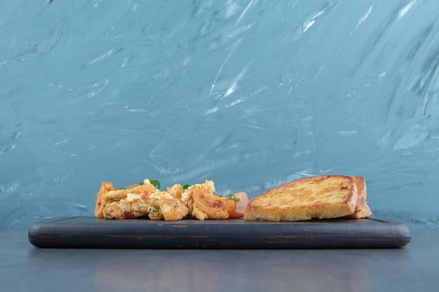 Jajka sadzone i kromki chleba na czarnej płycie.
