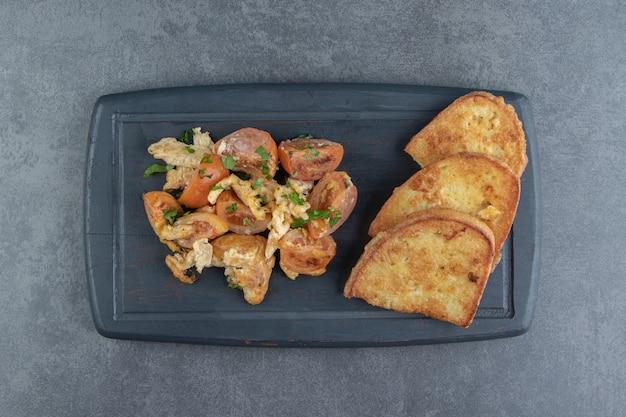 Jajka sadzone i kromki chleba na czarnym talerzu