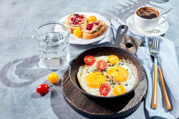 Jajka sadzone. jajka sadzone z dwóch jajek na żeliwnej patelni z pomidorkami koktajlowymi i mikro zieleniną, tostami i filiżanką kawy. koncepcja śniadanie słoneczny poranek