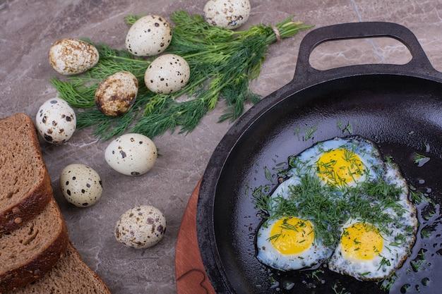 Jajka sadzone na metalowej patelni z ziołami.