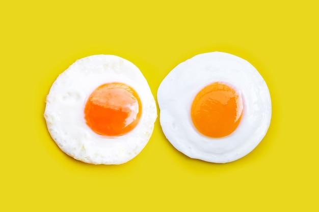 Jajka sadzone na żółtym tle. widok z góry