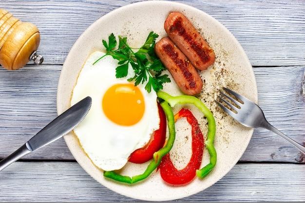 Jajka sadzone słoneczną stroną do góry z kiełbaskami i warzywami na lekkim drewnianym widelcu i nożu z góry