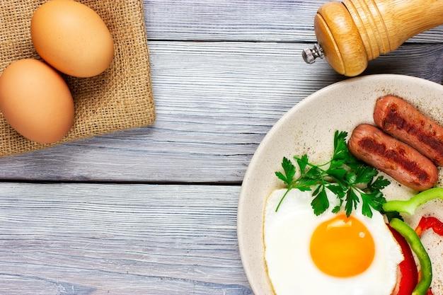 Jajka sadzone słoneczna strona z kiełbaskami i warzywami na jasnym drewnianym stole z widokiem