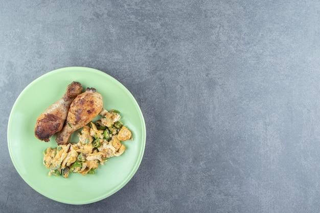 Jajka sadzone w głębokim tłuszczu i udka z kurczaka na zielonym talerzu.