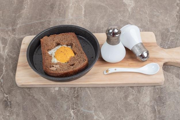 Jajka sadzone wewnątrz kromki chleba tostowego na czarnej płycie. wysokiej jakości zdjęcie