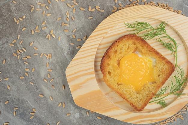 Jajka sadzone wewnątrz kromki chleba tostowego na drewnianym talerzu. wysokiej jakości zdjęcie