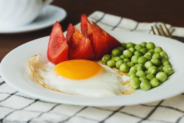 Jajka sadzone z groszkiem i pomidorami na białym talerzu