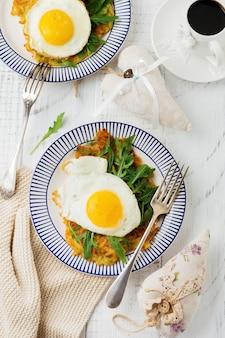 Jajka sadzone z plackiem ziemniaczanym, rukolą i awokado na talerzu ceramicznym na śniadanie na tle biały drewniany stół. widok z góry.