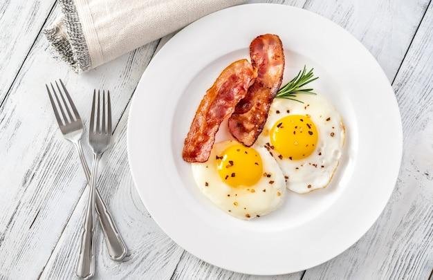 Jajka sadzone z plastrami boczku na białym talerzu