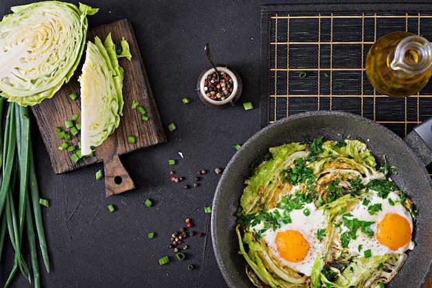 Jajka sadzone z plastrami młodej kapusty i zieleni. pożywne śniadanie. widok z góry. leżał płasko
