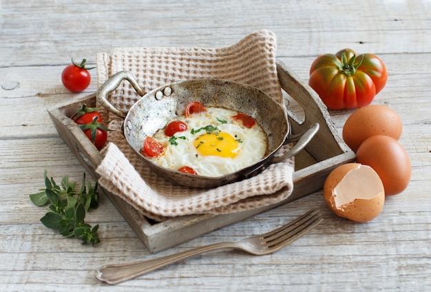 Jajka sadzone z pomidorami i ziołami na starej patelni na drewnie