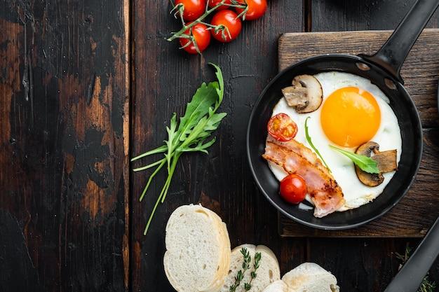 Jajka sadzone z pomidorkami koktajlowymi i chlebem na śniadanie na patelni żeliwnej, na starym ciemnym tle drewnianego stołu, płaski widok z góry, z miejscem na tekst copyspace