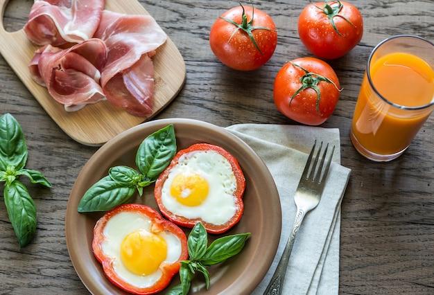 Jajka sadzone z prosciutto na drewnianym stole
