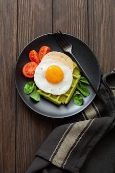 Jajka sadzone z serem, pomidorami, boćwią i goframi ze szpinakiem na czarnym talerzu ceramicznym na brązowym starym drewnianym stole. kanapka na śniadanie. selektywna ostrość. widok z góry. skopiuj miejsce.