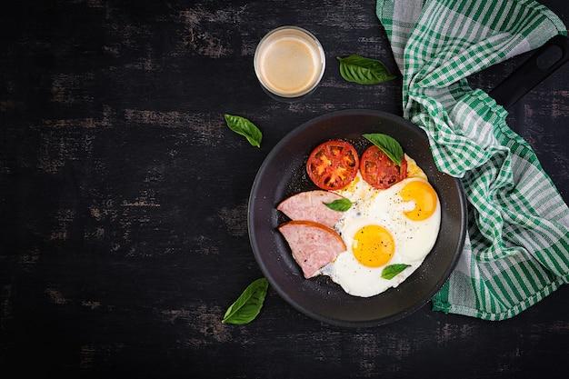 Jajka sadzone z szynką i pomidorami. pyszne śniadanie angielskie. późne śniadanie. keto, dieta paleo. widok z góry, nad głową