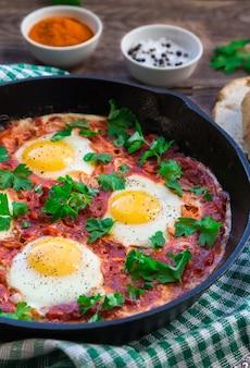 Jajka sadzone z warzywami i sosem pomidorowym na żelaznej patelni na rustykalnym drewnianym stole. tradycyjne izraelskie danie shakshuka. zdrowe śniadanie. selektywna ostrość.