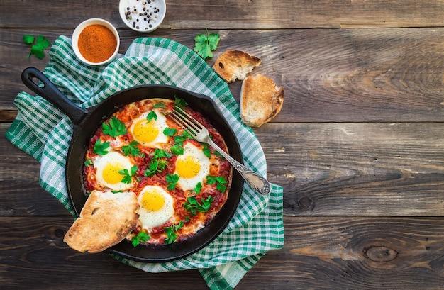 Jajka sadzone z warzywami i sosem pomidorowym na żelaznej patelni na rustykalnym drewnianym stole. tradycyjne izraelskie danie shakshuka. zdrowe śniadanie. widok z góry.