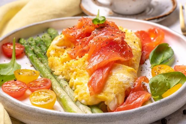 Jajka sadzone z zielonymi szparagami i łososiem, pomidorkami koktajlowymi i świeżym szpinakiem.